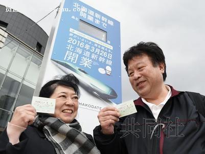 3月25日下午,一对夫妇在倒计时牌前高兴地拿出前往东京的北海道新干线首趟列车的车票。(共同社)